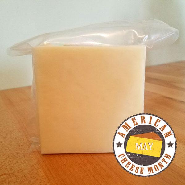 A brick of medium cheddar cheese.