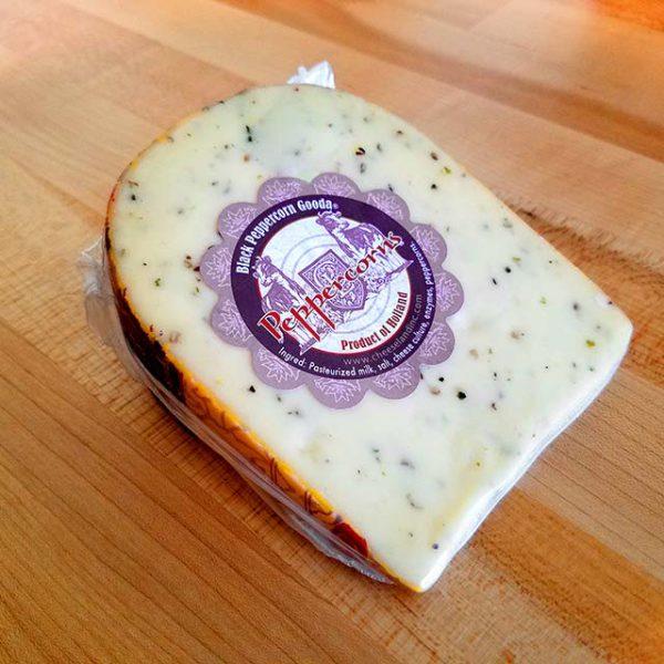 A wedge of Black Peppercorn Gouda cheese.