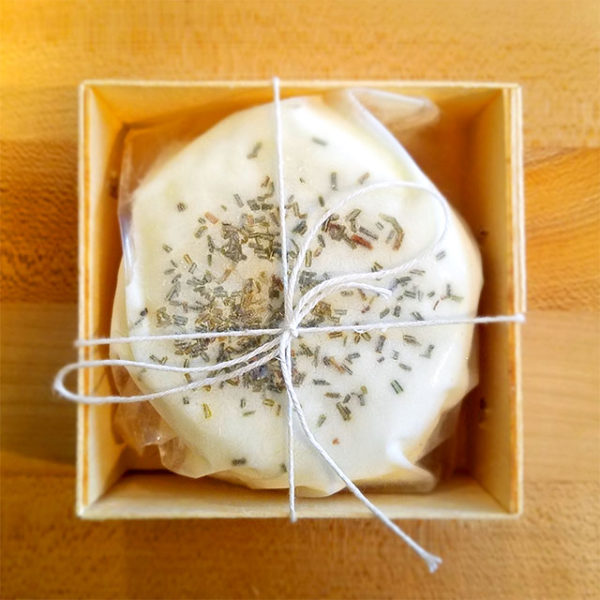 A boxed 5 oz. disc of Hidden Pastures Dairy Rosemary Chevre.