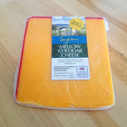 A wedge of Singleton's Mellow Cheddar cheese.