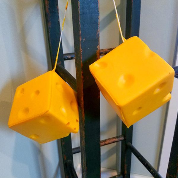 A pair of yellow rear view mirror dice made of foam that looks like real cheese.
