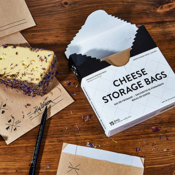 An open box of Formaticum Cheese Storage Bags on a table next to a wedge of cheese.