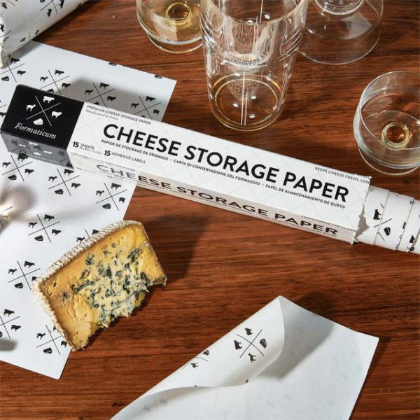 An open box of Formaticum Cheese Storage Paper on a table next to a wedge of cheese.