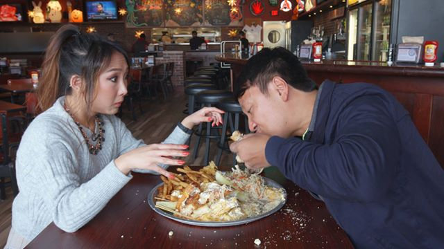 Two people partaking in the 14-cheese grilled cheese sandwich challenge in Cleveland.