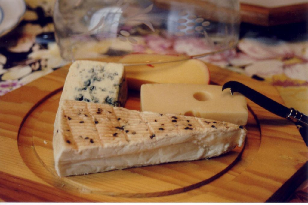 A wooden plate with assorted cheeses on it.