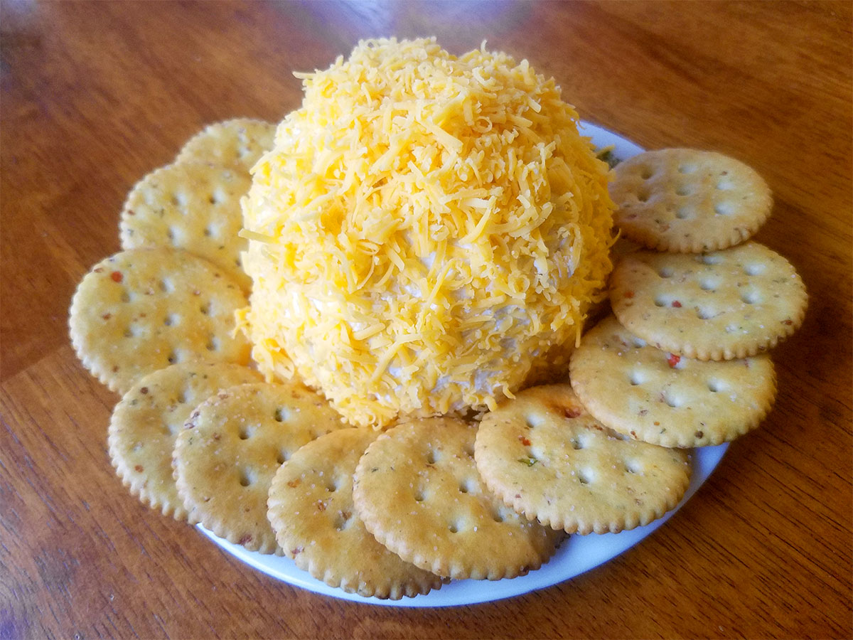 A cheese ball on a plate, surrounded by crackers.