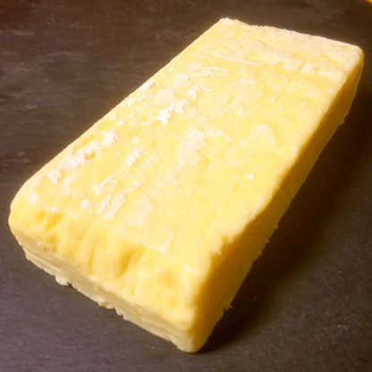 An unwrapped block of Tickler Extra Mature Devonshire Cheddar cheese.