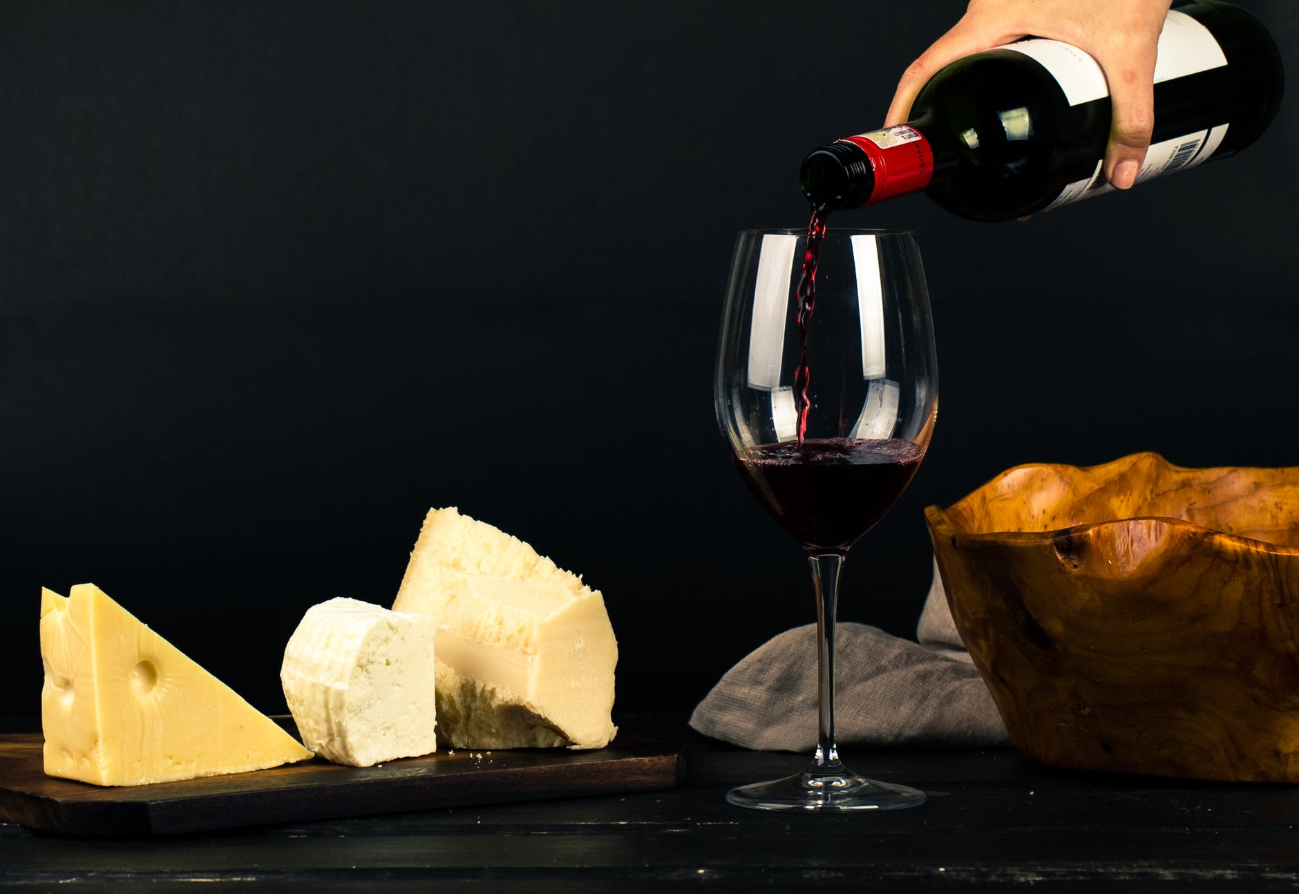 Photo of person pouring wine into glass beside some cheese pairings.