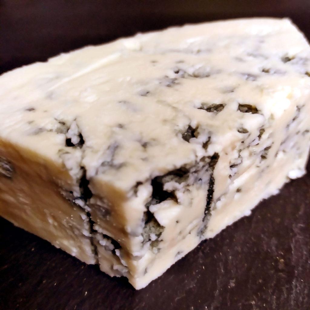 An unwrapped wedge of Danablu cheese.