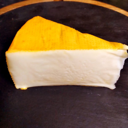 An unwrapped wedge of Port Salut cheese.