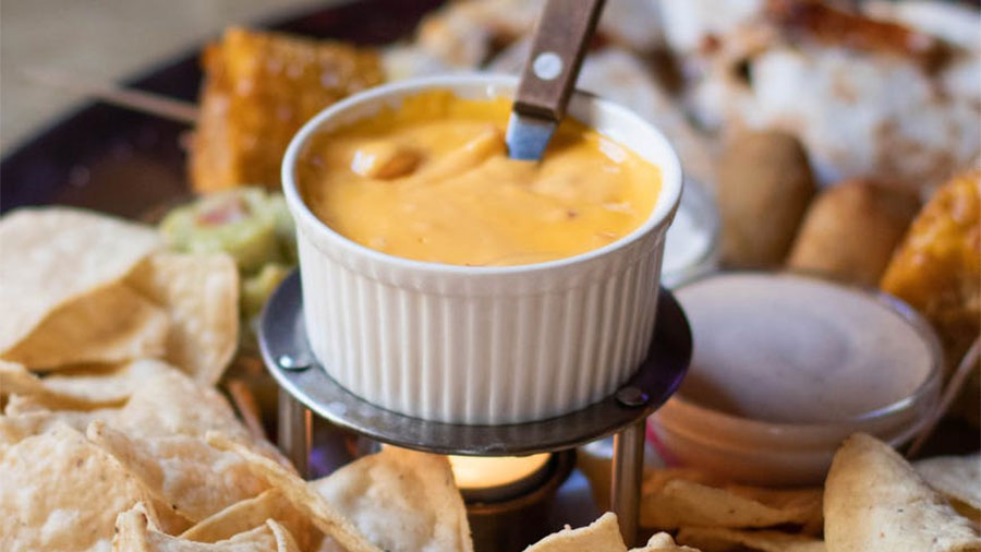 Tray of chips with queso dip.