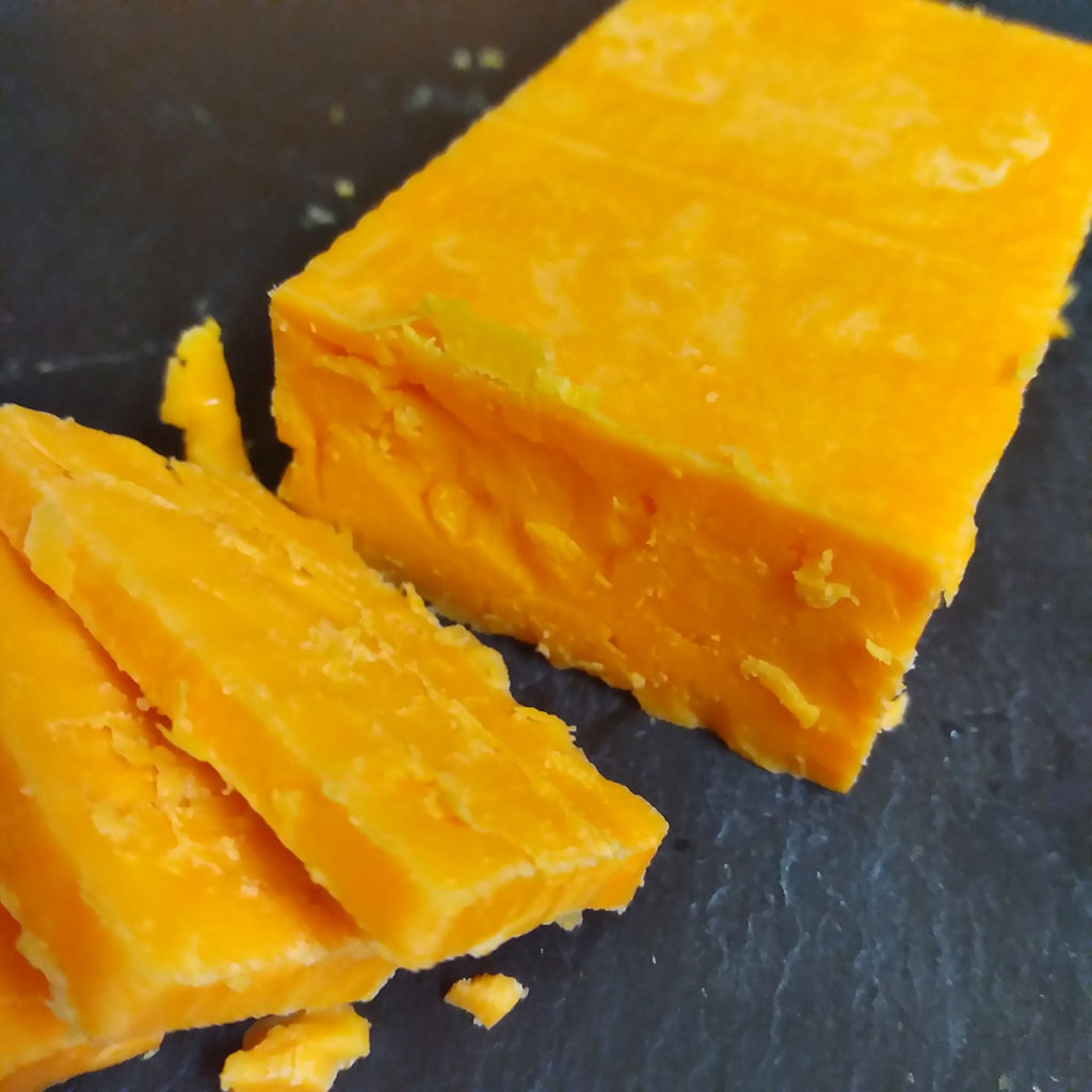 A cut up block of Red Fox Aged Red Leicester cheese.