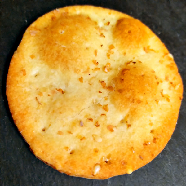 A single Ines Rosales Manchego Mini Tortas cracker.