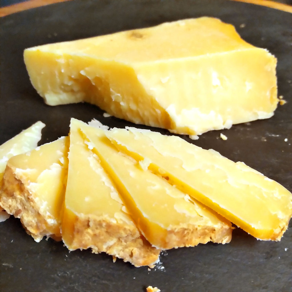 A cut up block of Jasper Hill Cave Aged Cheddar cheese.