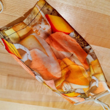 Closeup view of PPE face mask with cheese-patterned fabric.