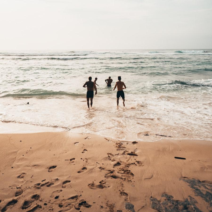 People Running Near Seashore at Daytime