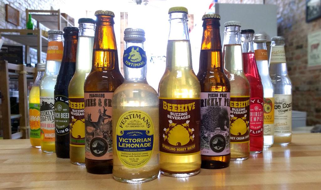 An assortment of soft drinks in glass bottles.